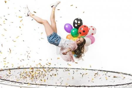 smiling girl holding colorful balloons and falling on trampoline isolated on white
