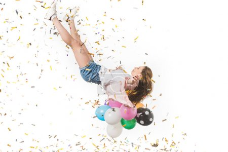 young woman with colorful balloons and shiny confetti falling isolated on white