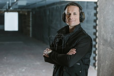 Photo for Smiling handsome man with crossed arms looking at camera in shooting range - Royalty Free Image