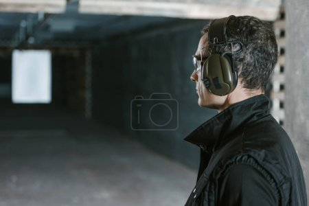 Photo for Side view of handsome man looking at target in shooting range - Royalty Free Image