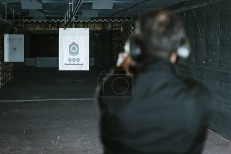 rear view of man aiming gun at target in shooting range
