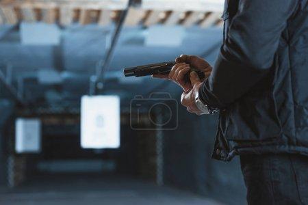 Cropped image of man putting magazine into gun...