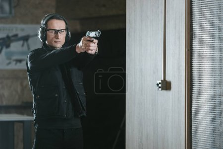 Photo for Handsome man aiming gun at target in shooting range - Royalty Free Image