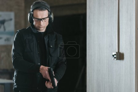 Photo for Handsome man looking at gun in shooting range - Royalty Free Image