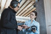 instructor pointing on ear muffs in shooting range