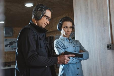 female client standing with crossed arms in shooting range