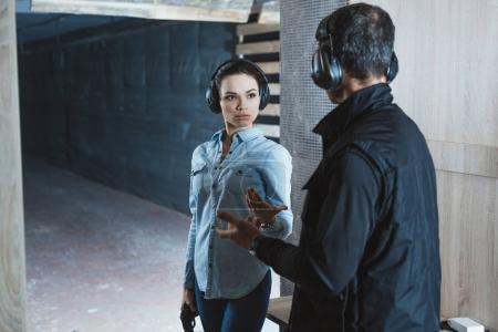 Foto de Mujer al cliente hablando con hombre instructor de tiro - Imagen libre de derechos