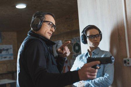 Photo pour Instructeur masculin pointant sur quelque chose dans la Galerie de tir - image libre de droit