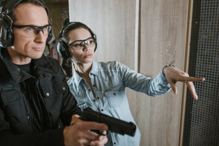 female customer pointing on something in shooting gallery