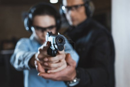 Photo for Instructor helping customer in shooting gallery with gun on foreground - Royalty Free Image