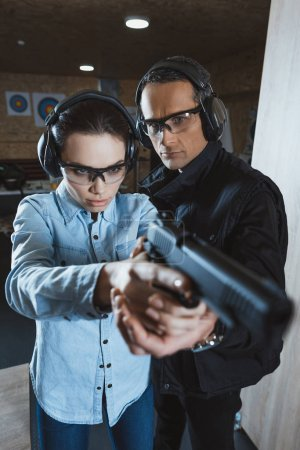Photo for Instructor helping customer holding gun - Royalty Free Image