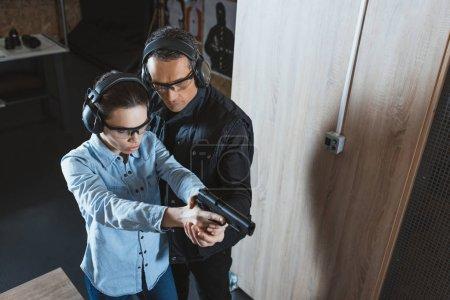 Foto de Vista aérea de instructor ayudando al cliente en la galería de tiro - Imagen libre de derechos