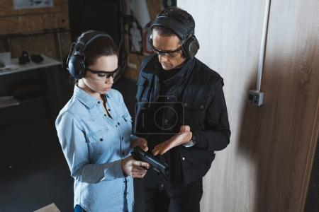 Photo for Male instructor describing gun to female customer in shooting range - Royalty Free Image