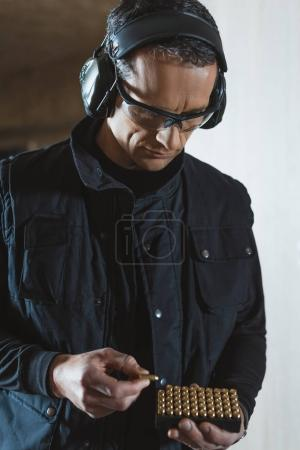 handsome man taking bullet from box