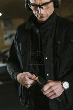 handsome man putting bullet into rifle magazine