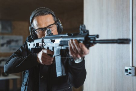 handsome man aiming rifle in shooting range