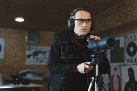 man fixing binoculars in shooting range