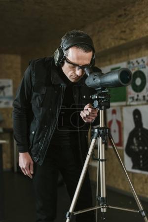 Photo pour Homme regardant à travers les jumelles à distance cible dans le champ de tir - image libre de droit