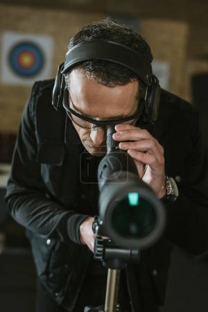 man looking through binoculars in shooting range
