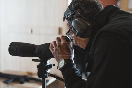 Photo for Man looking through binoculars in shooting range - Royalty Free Image