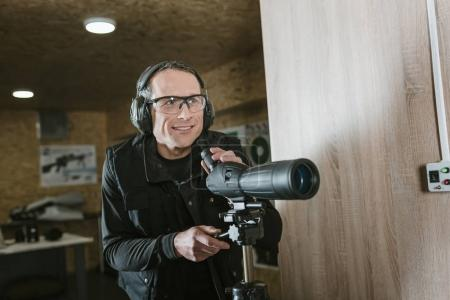 smiling man with binoculars in shooting range