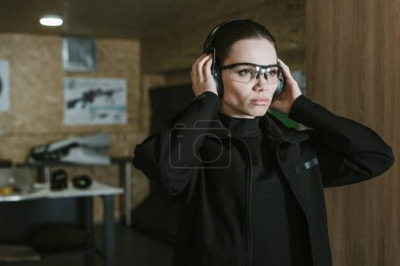attractive girl wearing hearing protectors in shooting range