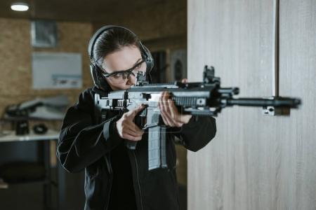 Photo pour Fille visant fusil dans le champ de tir - image libre de droit