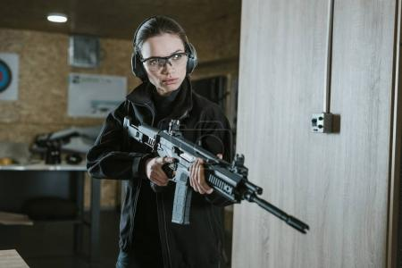 Photo for Attractive girl with safety glasses and headphones holding rifle - Royalty Free Image