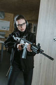 attractive girl with safety glasses holding rifle