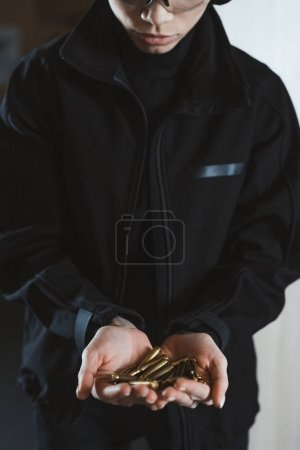 cropped image of woman holding rifle bullets in hands