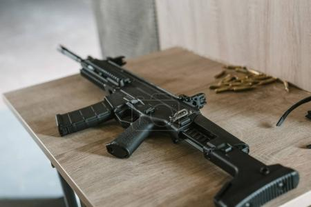 black rifle with bullets on wooden table in shooting range