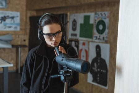 Photo for Attractive woman with binoculars in shooting range - Royalty Free Image