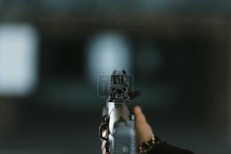 Photo for Cropped image of man aiming rifle at target in shooting range - Royalty Free Image