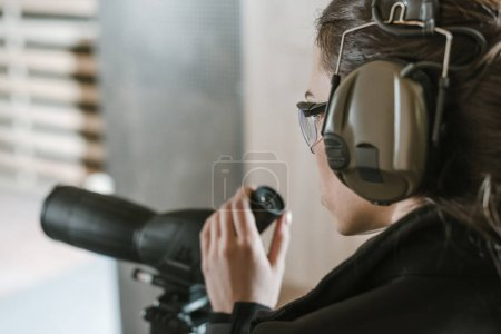 Photo for Side view of woman with binoculars in shooting range - Royalty Free Image