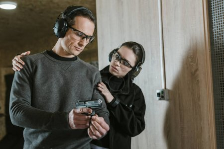 instructor helping client to stand with gun in shooting range