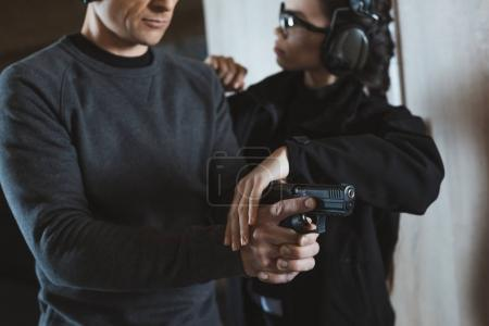 Photo for Cropped image of instructor describing client how to hold gun - Royalty Free Image