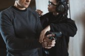 cropped image of instructor describing client how to hold gun