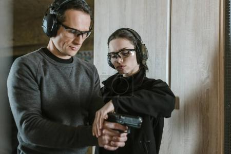 Photo for Instructor describing client how to hold gun - Royalty Free Image