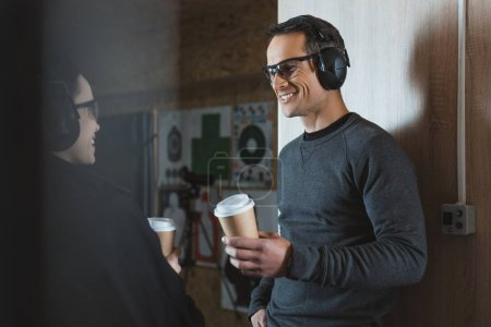 Photo for Smiling customer and shooting instructor drinking coffee in shooting range - Royalty Free Image
