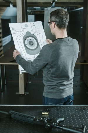 rear view of shooter looking at used target after shooting in shooting range