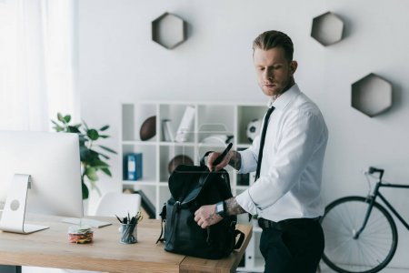 handsome young tattooed businessman with backpack looking down in office