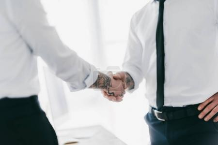 cropped shot of young business people shaking hands