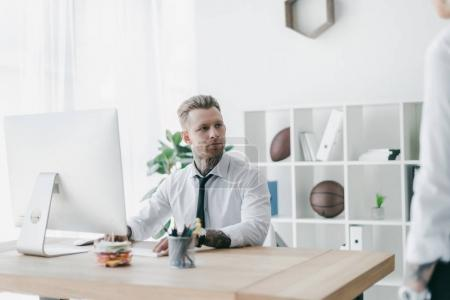 Photo for Handsome young tattooed businessman looking away while working with desktop computer in office - Royalty Free Image