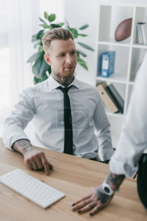 selective focus of handsome young businessman looking at colleague at workplace