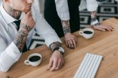 cropped shot of young business people with tattoos working together at table