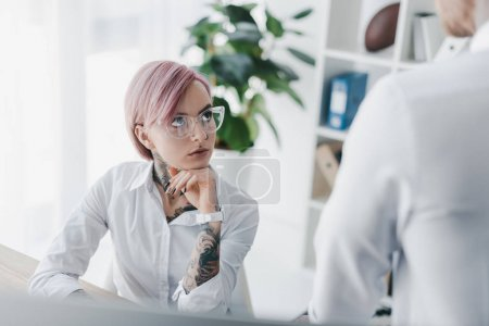 cropped shot of serious young businesswoman looking at colleague in office
