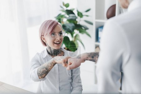 cropped shot of young business people in tattoos gesturing fist bump in office