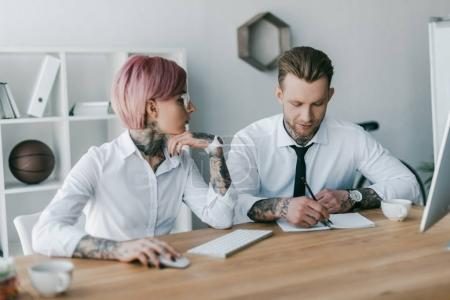 young businesswoman looking at male colleague taking notes at workplace