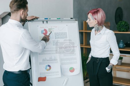 young business colleagues working with charts on whiteboard