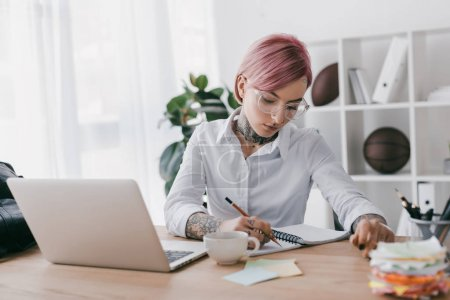 junge tätowierte Geschäftsfrau macht sich Notizen, während sie Laptop am Arbeitsplatz benutzt